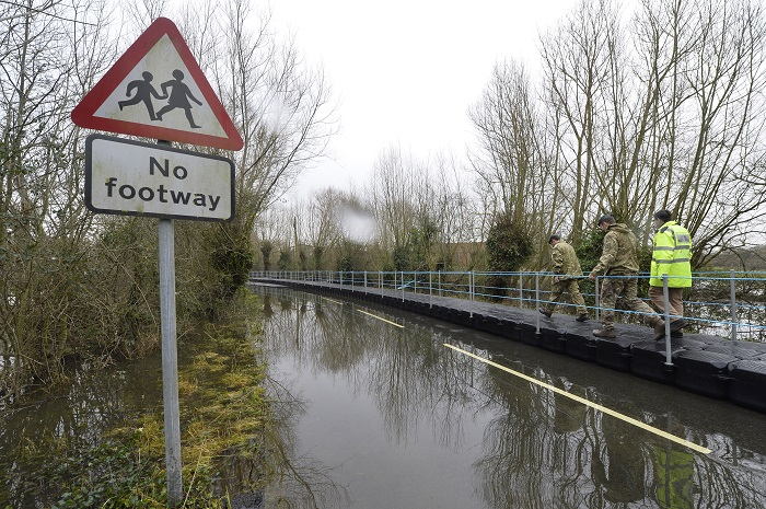 British Army Royal Engineers walk along a floating pontoon in flooded parts of Somerset.