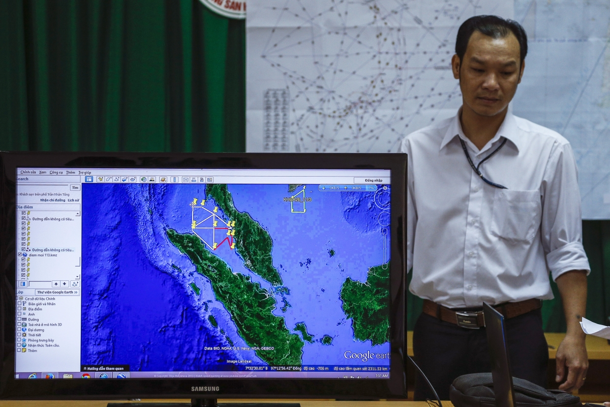 A Vietnamese officer stands next to a TV screen showing a flight route during a news conference about their mission to find missing Malaysia Airlines flight MH370