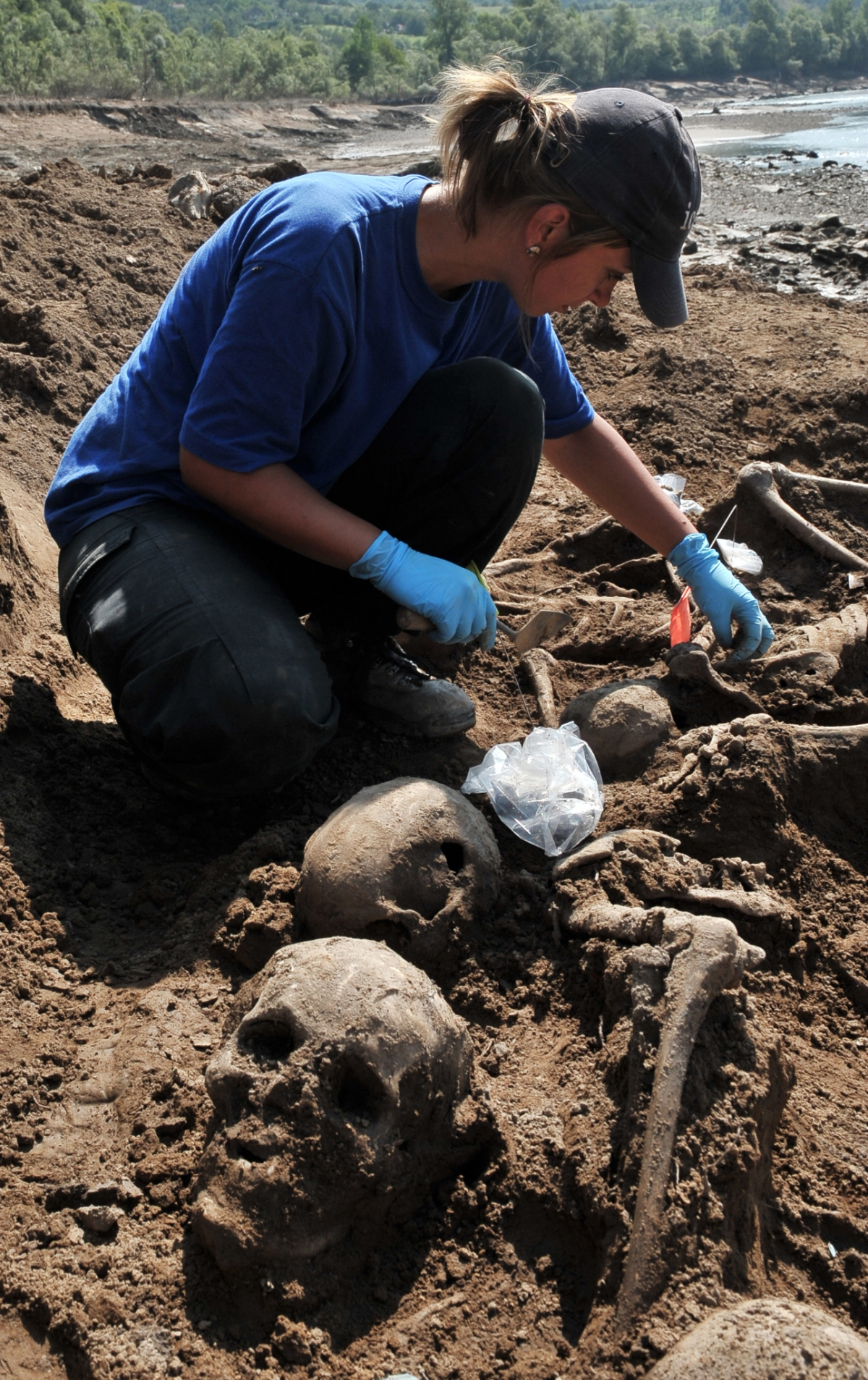 forensic expert from the International Commission On Missing Persons uncovers human remains near the eastern Bosnian town of Visegrad