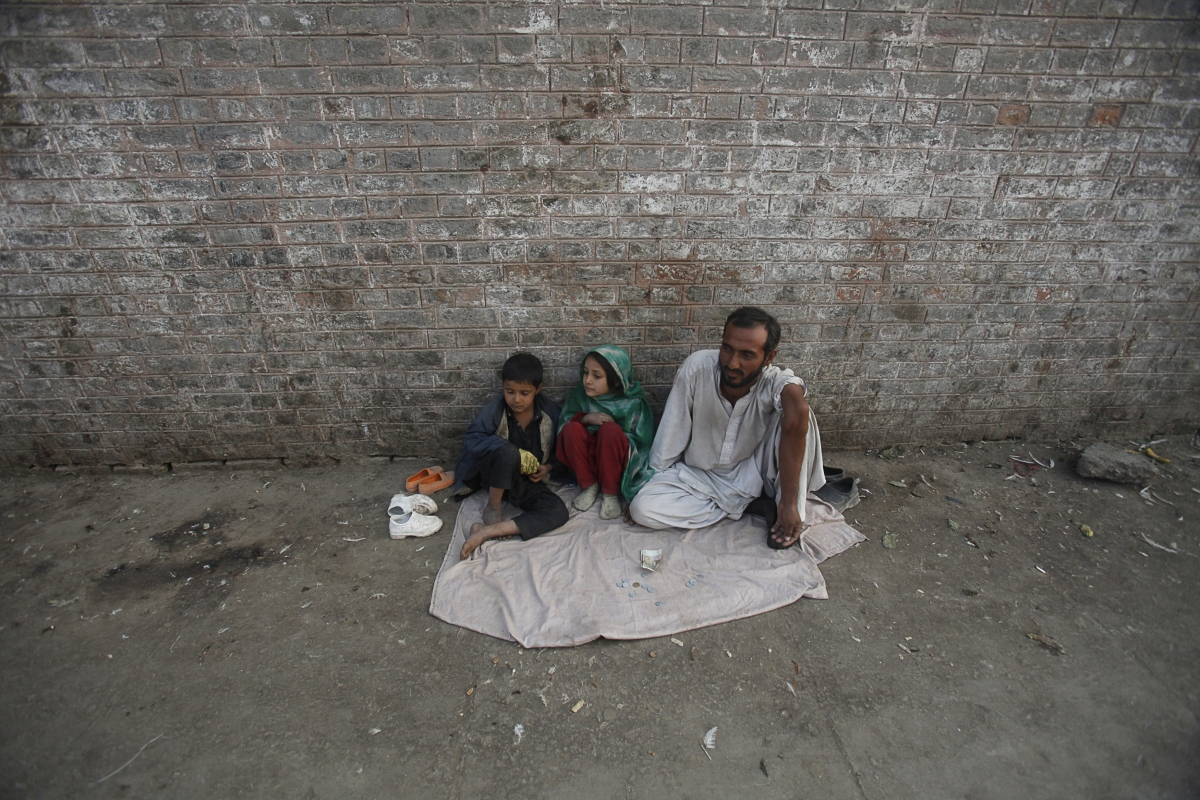 A man sits with his children as he begs along a sidewalk in P