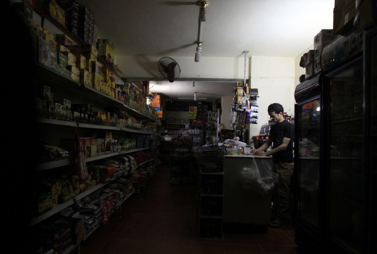 A supermarket seller stands near an emergency light during power outage