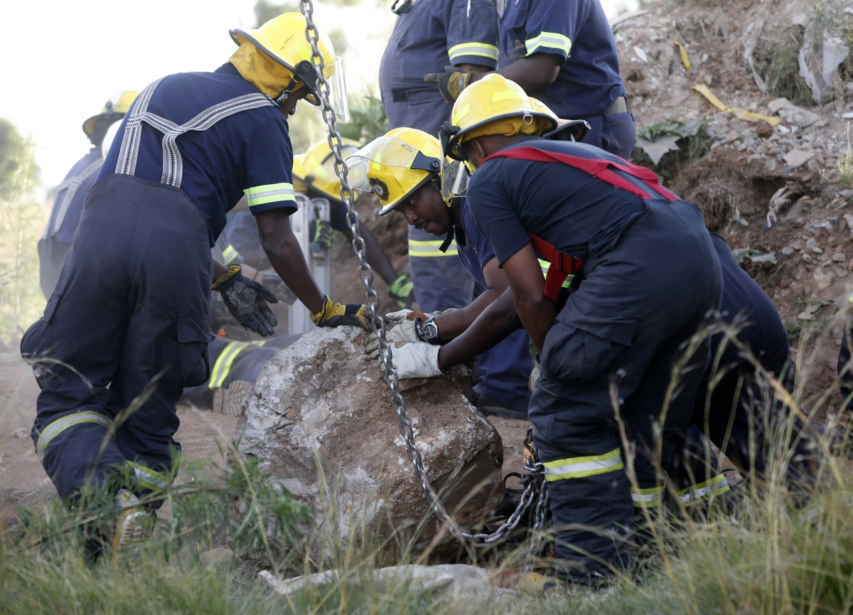 Rescue officials move a rock removed from an abandoned gold shaft as they work to rescue trapped suspected illegal miners in Benoni, east of Johannesburg