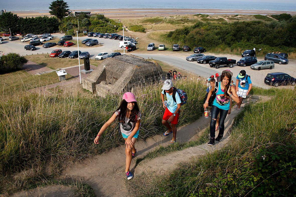 Jovens caminhar até uma colina passado um bunker alemão velho com vista para a antiga zona de desembarque do Dia D de Omaha Beach, perto de Colleville sur Mer, França