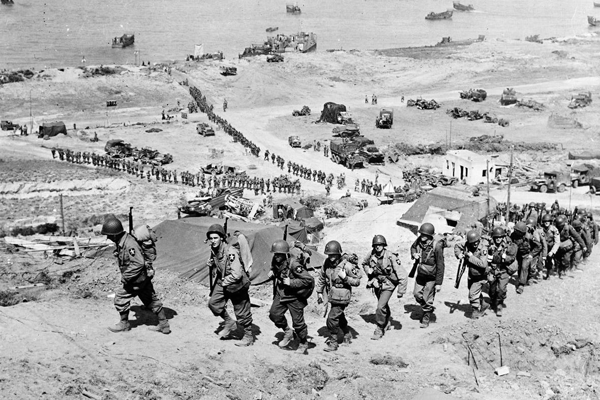 18 de junho de 1944: reforços do Exército dos EUA marchar até uma colina passado um bunker alemão com vista para praia de Omaha após os desembarques do Dia D perto de Colleville sur Mer, França