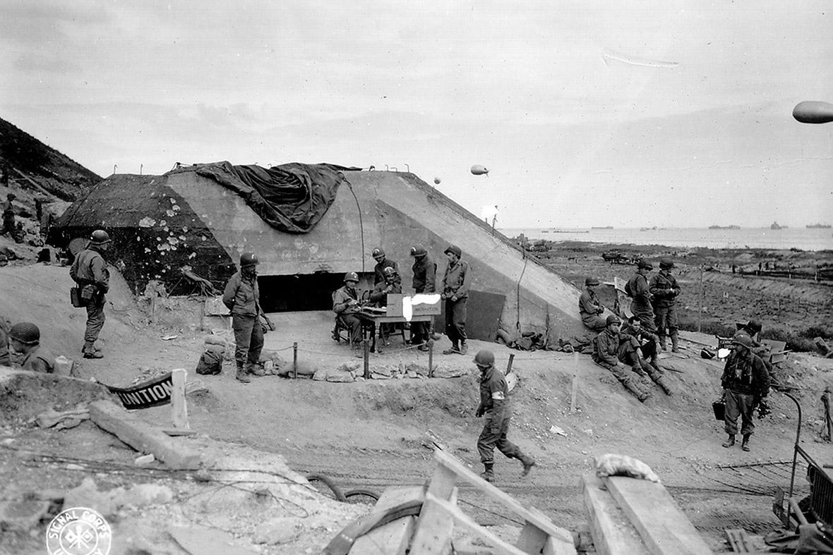 7 de junho de 1944: Tropas do Exército dos EUA se reúnem em torno de um poste de sinal usado por engenheiros no local de um bunker alemão capturado com vista para praia de Omaha após os desembarques do Dia D perto de Saint Laurent sur Mer