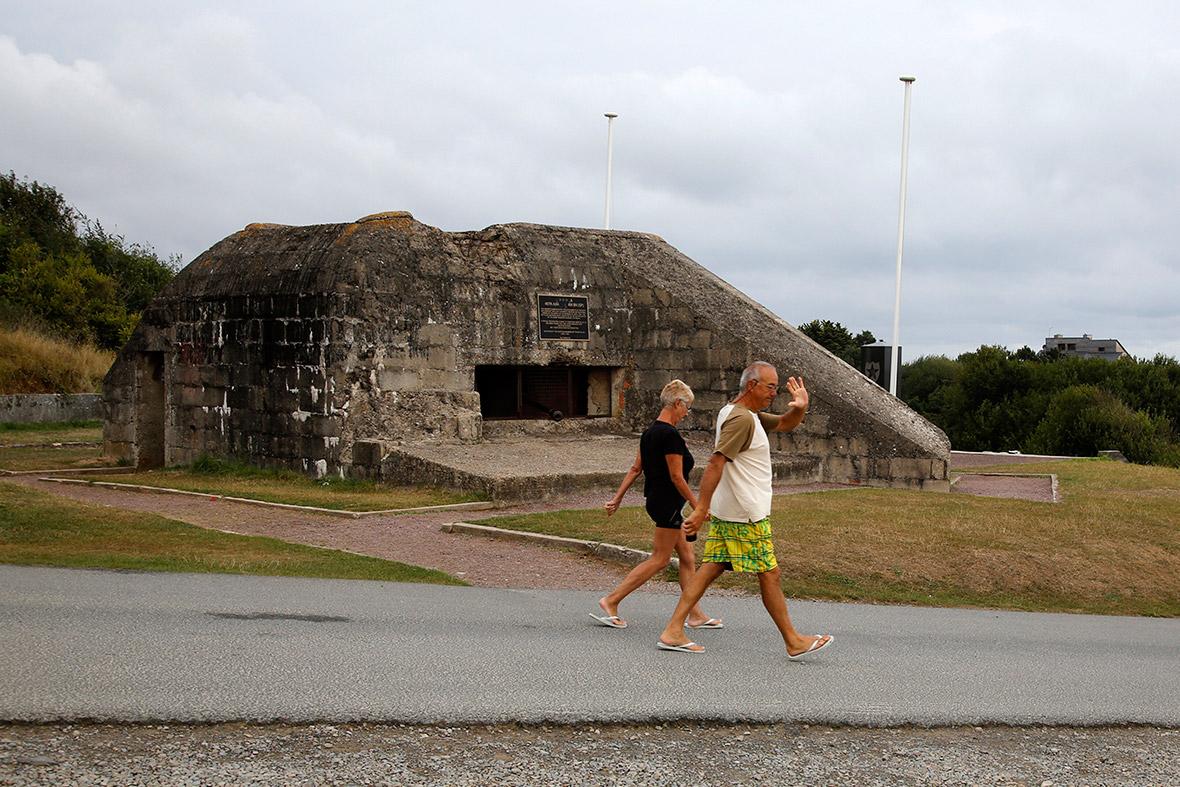 Os turistas andam após um ex-bunker de alemão com vista para a zona de desembarque do Dia D em Omaha Beach, perto de Saint Laurent-sur-Mer, França