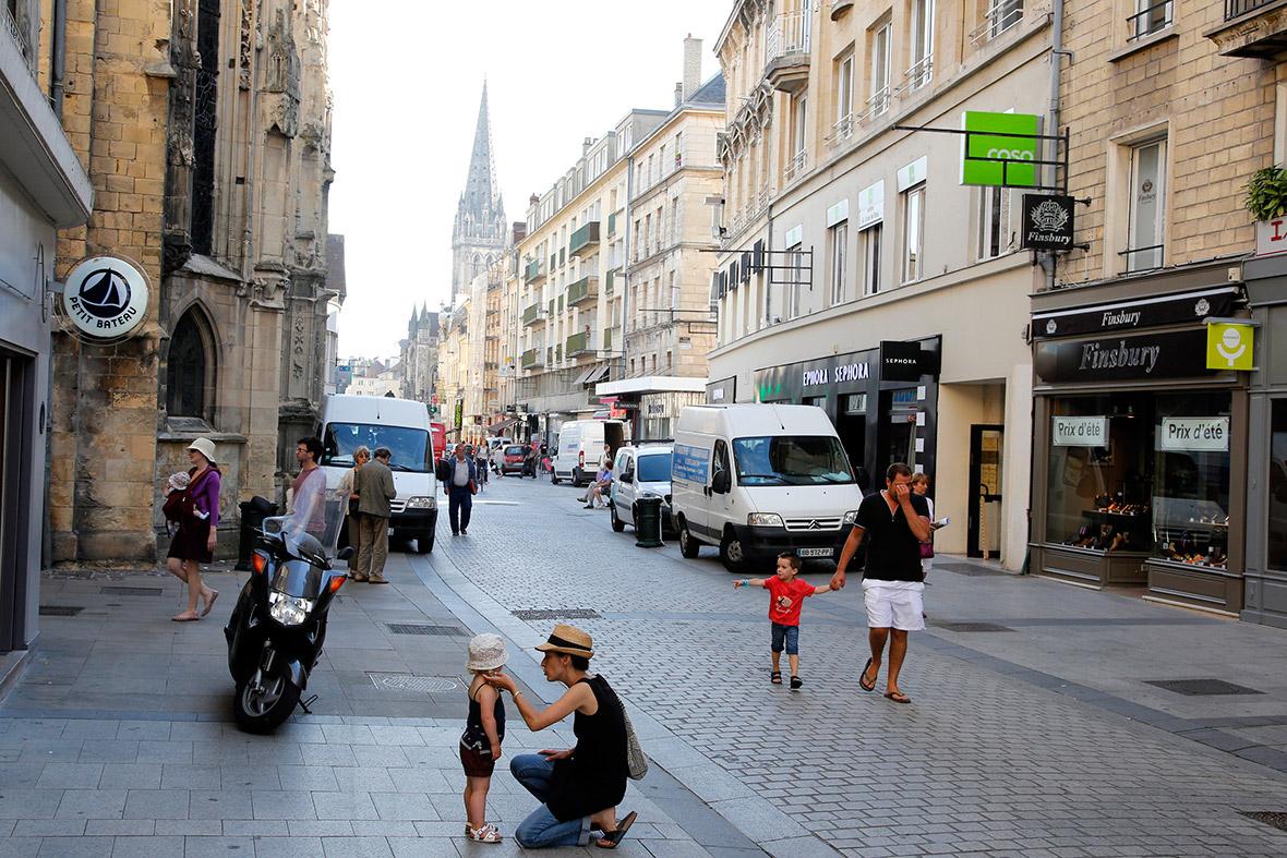 Os clientes andam ao longo da reconstruída Rue Saint-Pierre, em Caen, que foi destruída após os desembarques do Dia D