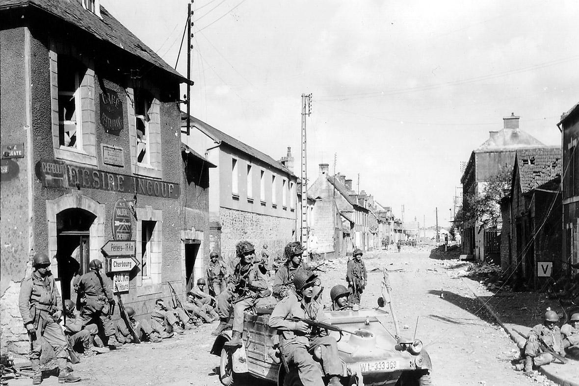 6 de junho de 1944: pára-quedistas do Exército dos EUA da 101 ª Divisão Aerotransportada dirigir um alemão Kubelwagen capturado no cruzamento da Rue Holgate e RN13 em Carentan, França