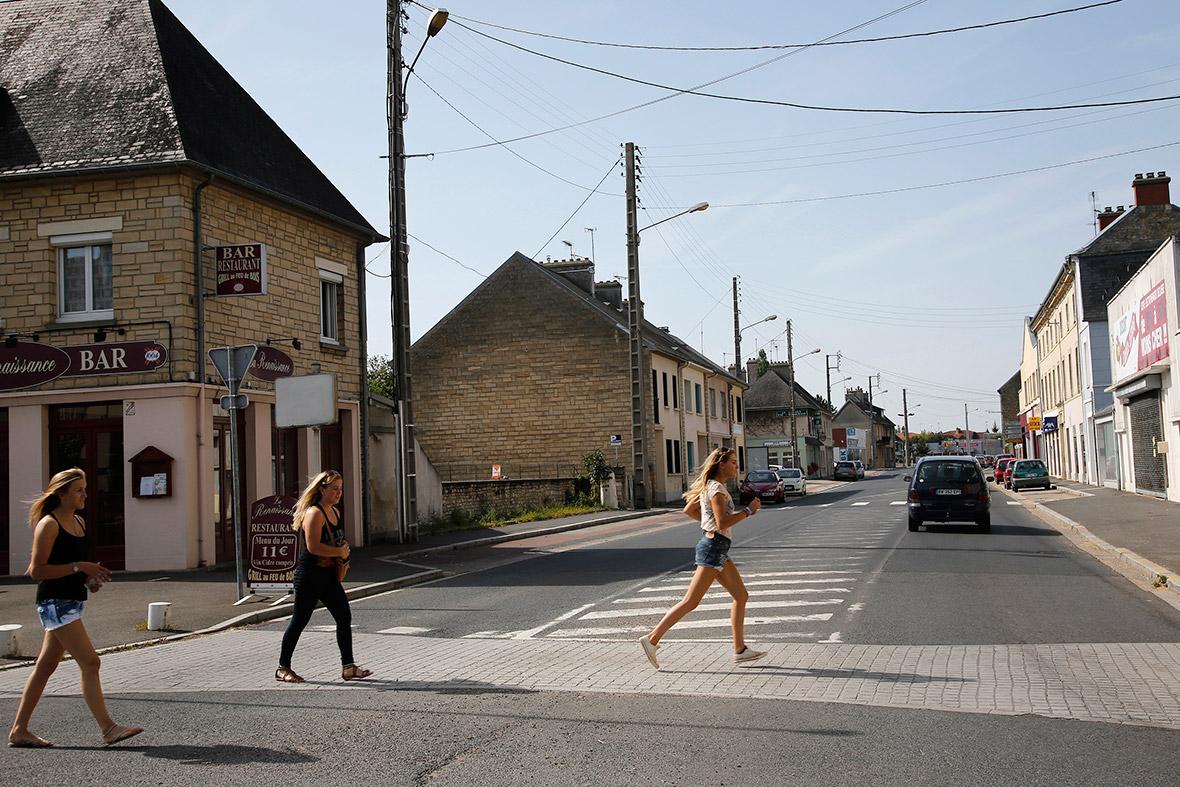 Meninas atravessam a rua no cruzamento da Rue Holgate e RN13 na Normandia cidade de Carentan, França
