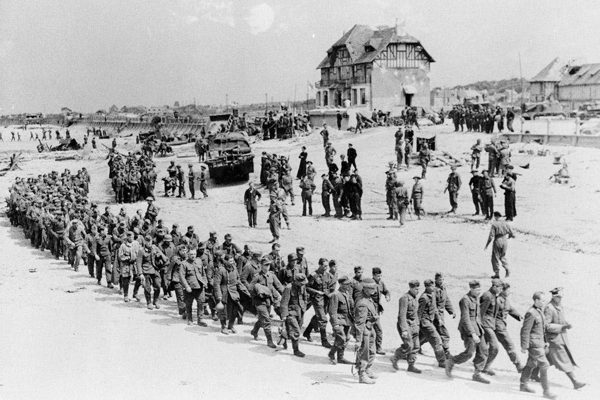 6 de junho de 1944: Alemão prisioneiros de guerra marcha ao longo da área de desembarque Juno Beach a um navio levando-os para a Inglaterra, depois que eles foram capturados por tropas canadenses no Bernieres Sur Mer, França