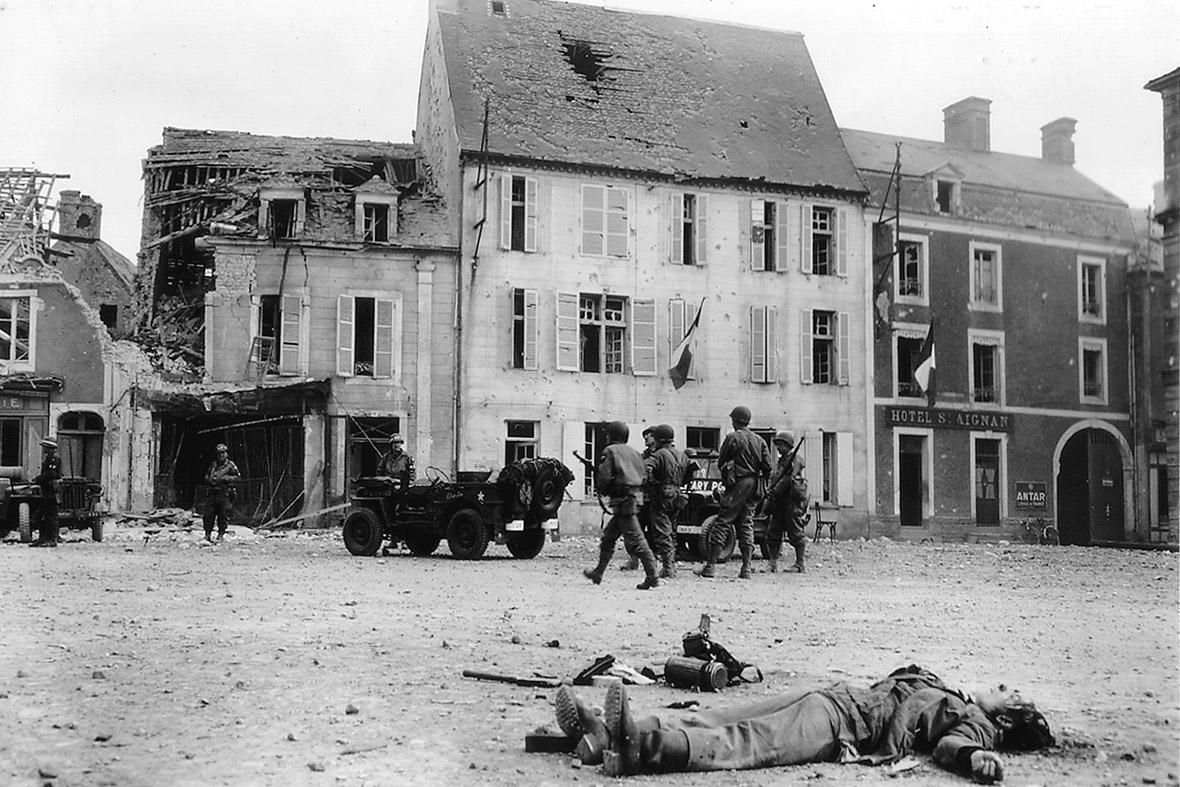 15 de junho de 1944: O corpo de um soldado alemão morto está na praça principal da Place du Marché em Trevieres após a cidade foi tomada pelas tropas americanas que desembarcaram na vizinha praia de Omaha