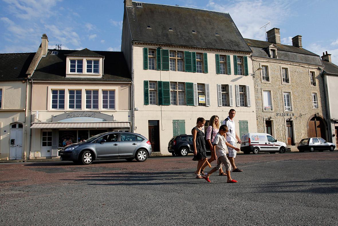 Turistas atravessar a praça principal da Place du Marché em Trevieres, perto da antiga zona de desembarque do Dia D da Omaha Beach
