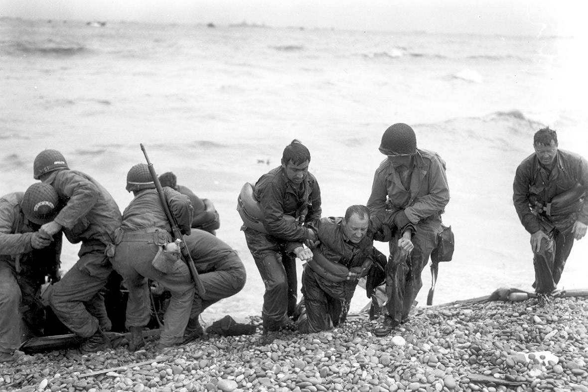 June 6, 1944: Members of an American landing party assist troops whose landing craft was sunk by enemy fire off Omaha beach, near Colleville sur Mer, France