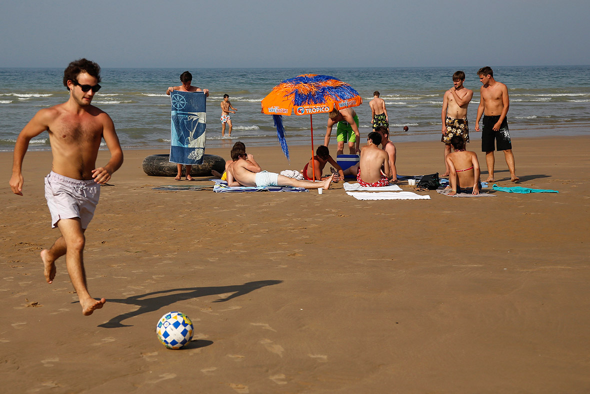 Holidaymakers enjoy the sunshine on the former D-Day landing zone of Omaha beach near Vierville sur Mer, France