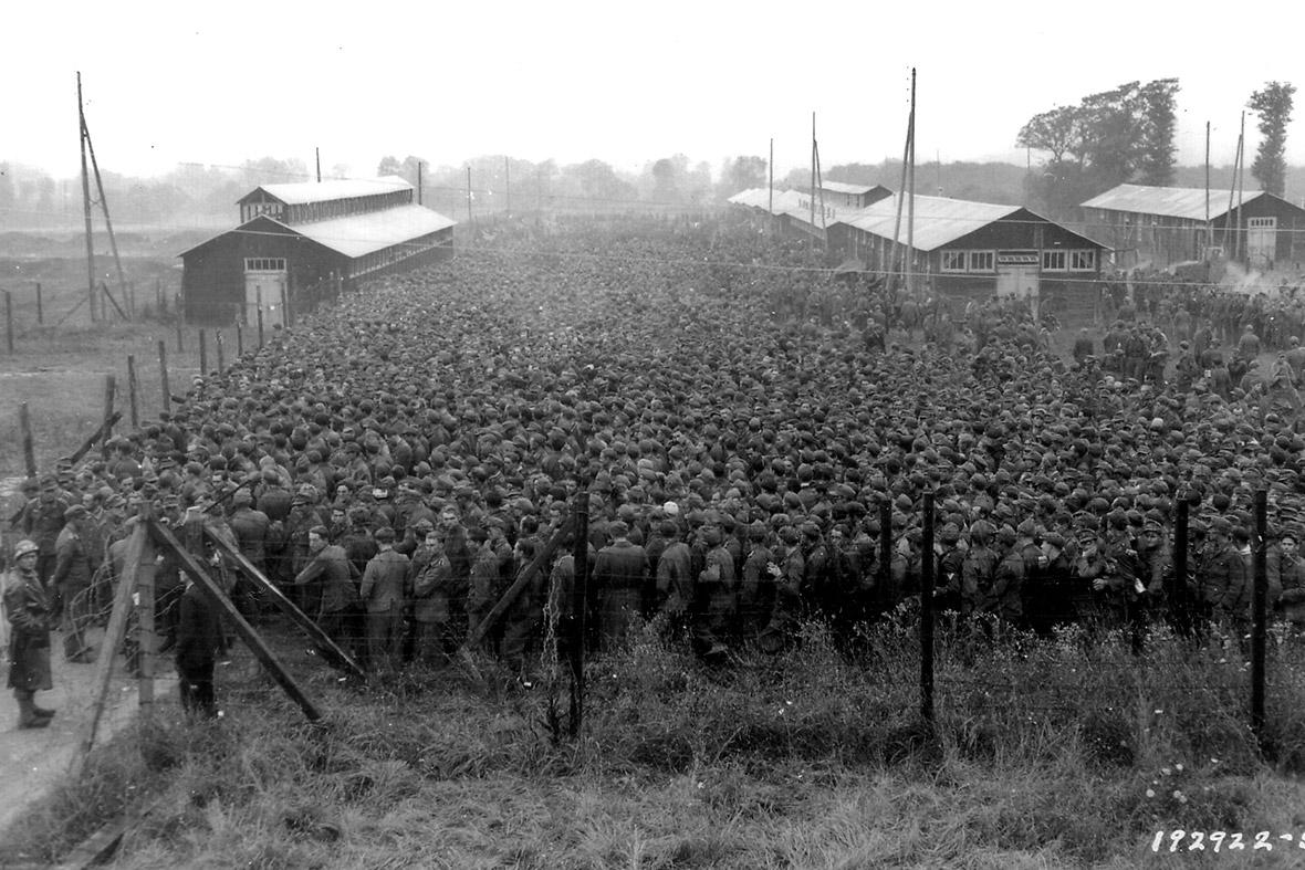 21 agosto de 1944: prisioneiros de guerra alemães capturados após os desembarques do Dia D na Normandia são guardados por soldados norte-americanos em um acampamento em Nonant-le-Pin, França