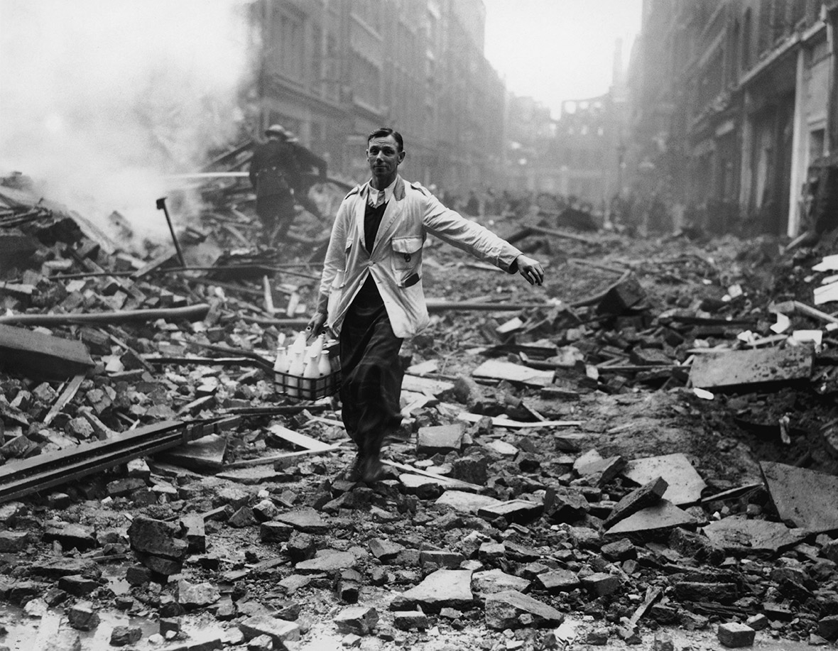 A milkman delivers milk in a London street devastated during a German bombing raid.  Firemen are dampening down the ruins behind him
