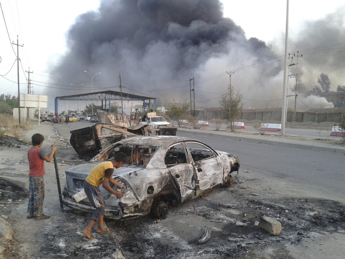 Civilian children stand next to a burnt vehicle during clashes between Iraqi security forces and al Qaeda-linked Islamic State in Iraq and the Levant (Isis) in the northern Iraq city of Mosul.