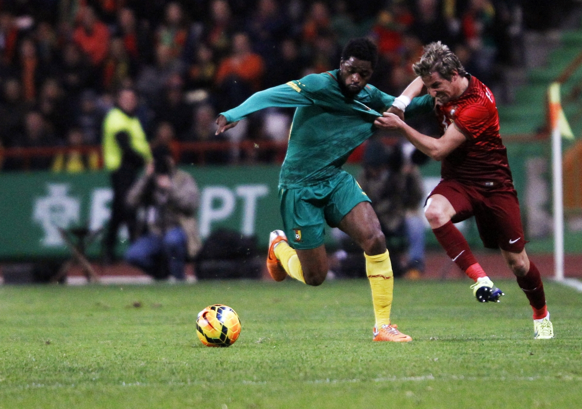 Portugal's Fabio Coentrao (R) fights for the ball with the Cameroon's Alex Song during their international friendly soccer match at Leiria stadium March 5, 2014.