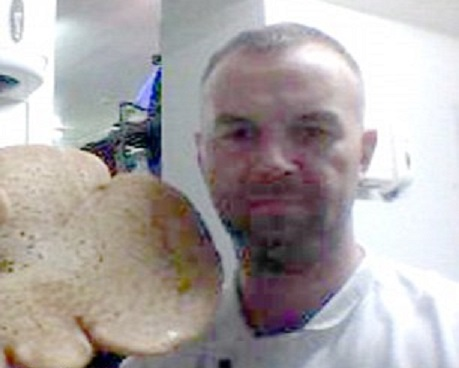Scott Mcmillan poses with baked creation before sacking by Donald Trump