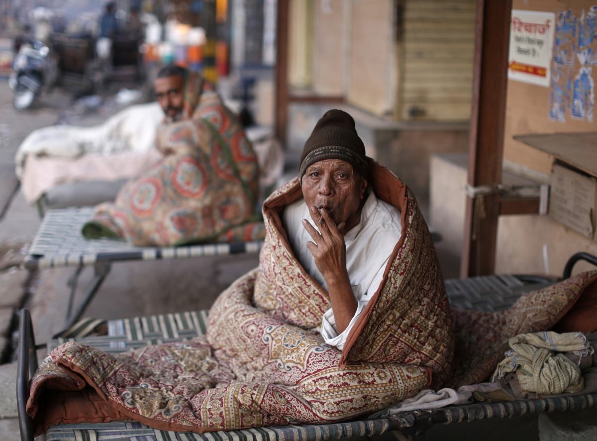 A homeless man smokes as he is wrapped in a quilt at a pavement early morning in the old quarters of Delhi