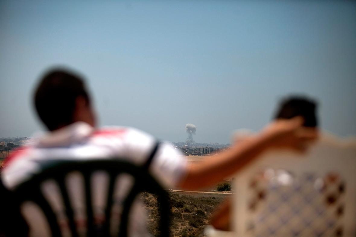 Israelis near Sderot watch a smoke plume rising over Gaza following an Israel Air Force bombingGetty