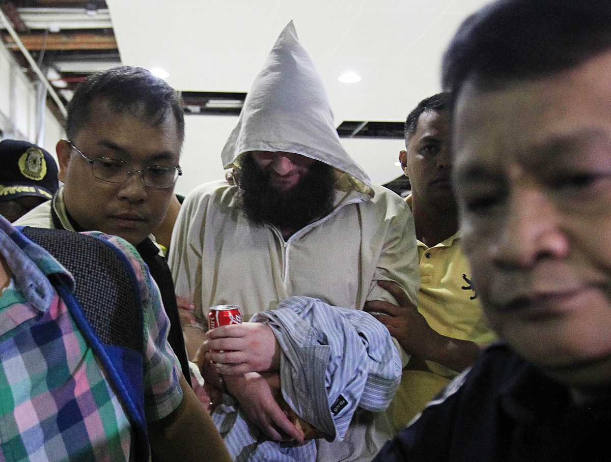 Cerantonio is led through manila Airport by Philippino authorities. (Reuters)