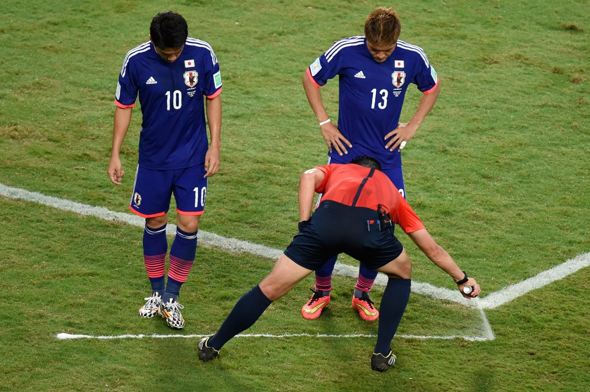 Portugues referee Pedro Proenca sprays a free kick line during a Group C football match between Japan and Colombia at the Fifa World Cup 2014