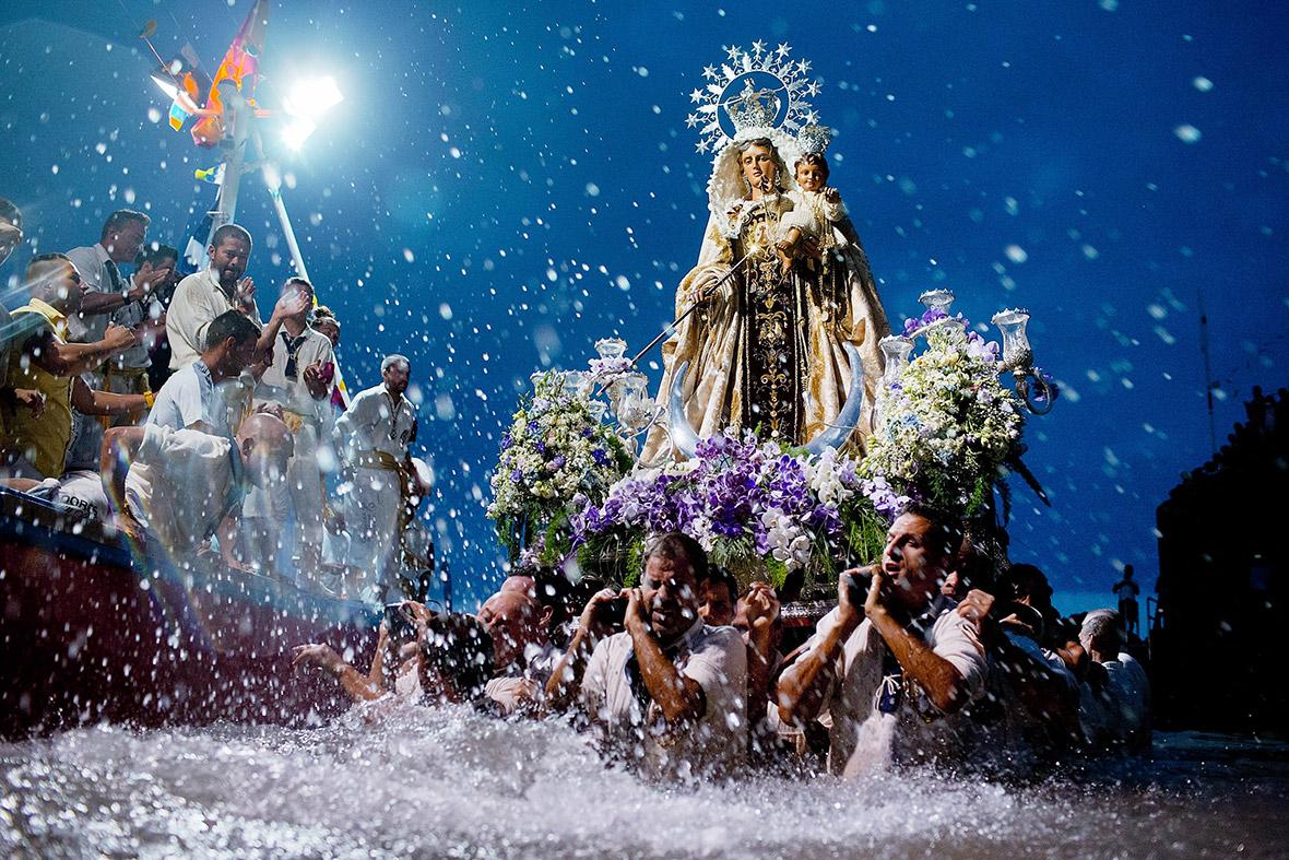 Men carry the statue of Virgen del Carmen to Puerto de la Cruz dock on ...