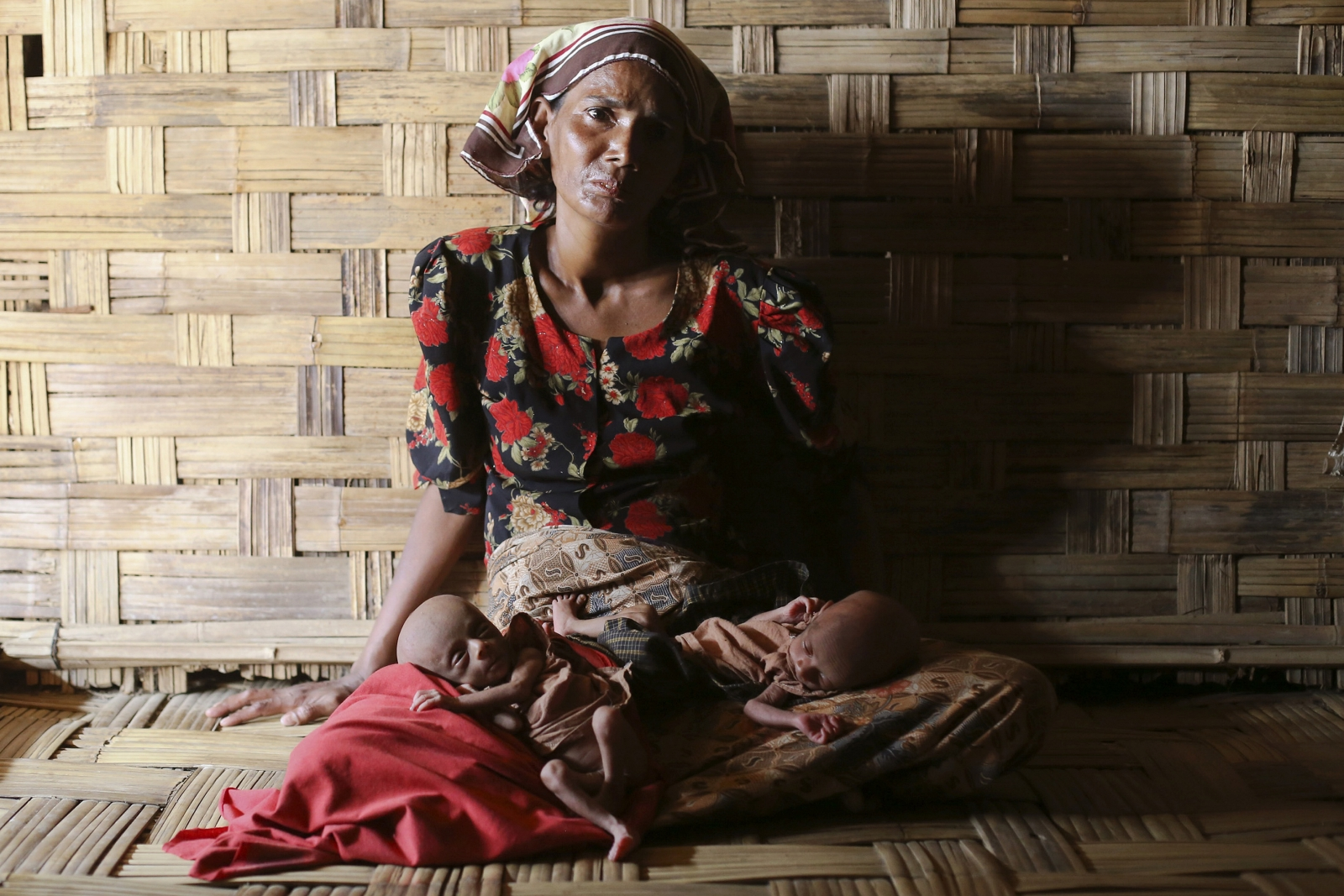 Displaced Rohingya woman Norbagoun carries her severely malnourished 25-day-old twins in her lap in their house at the Dar Paing camp for internally displaced people in Sittwe, Rakhine state