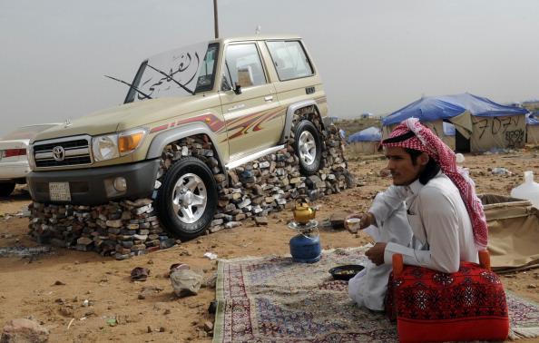 Saudi youth sits next to his SUV
