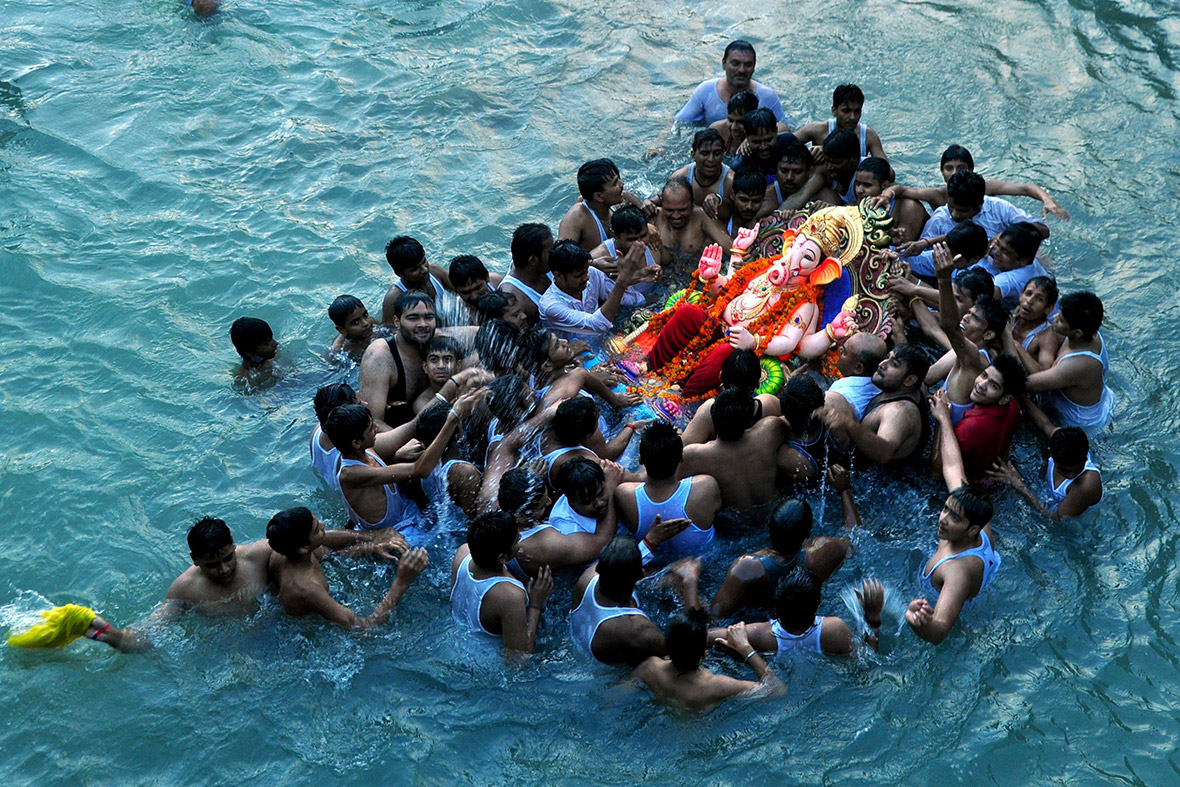 Indian Hindu devotees immerse a statue of the Hindu god Lord Ganesha in a river on the outskirts of Patiala during the ten-day Ganesh Chaturthi festival