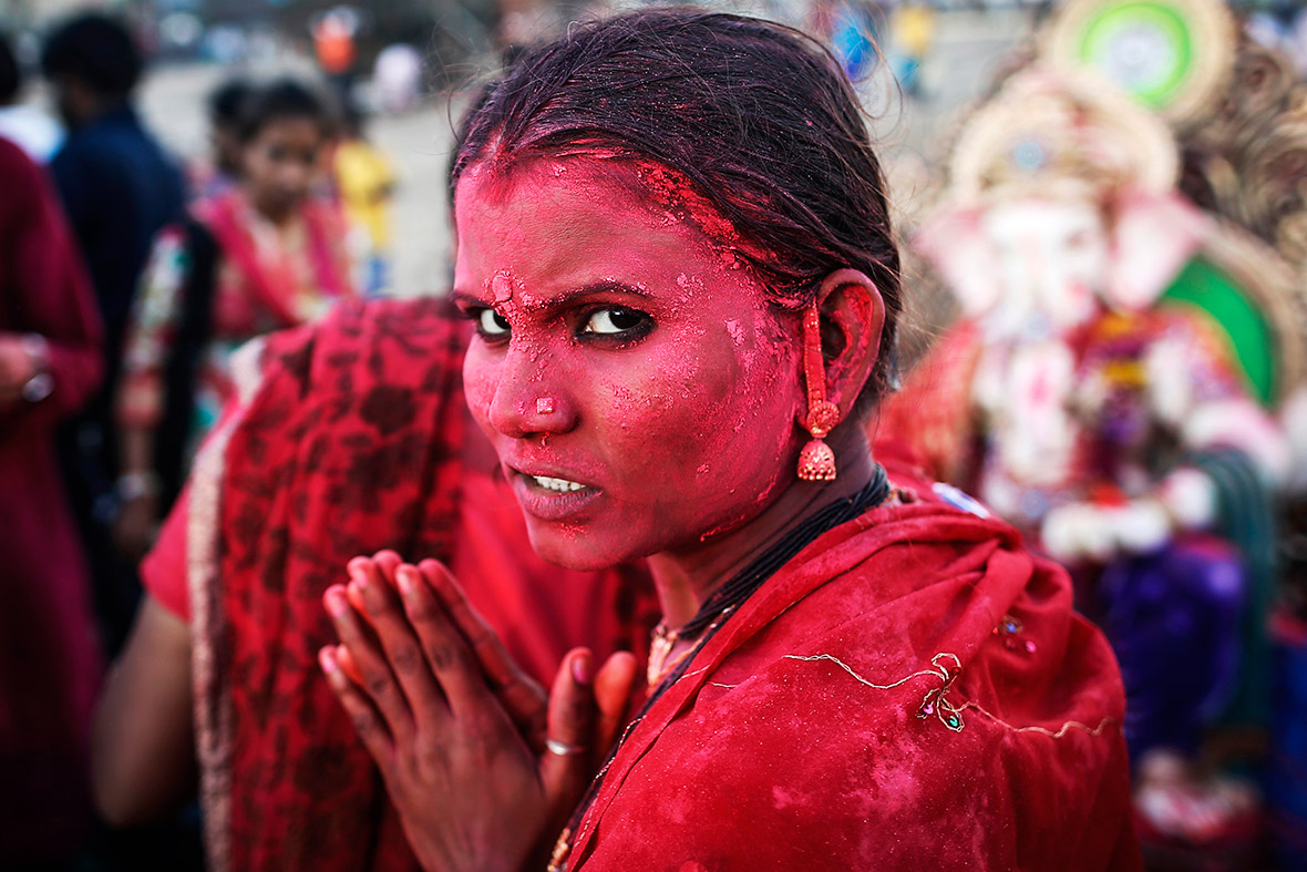 A devotee daubed in coloured powder takes part in the Ganesh Chaturthi festival in Mumbai