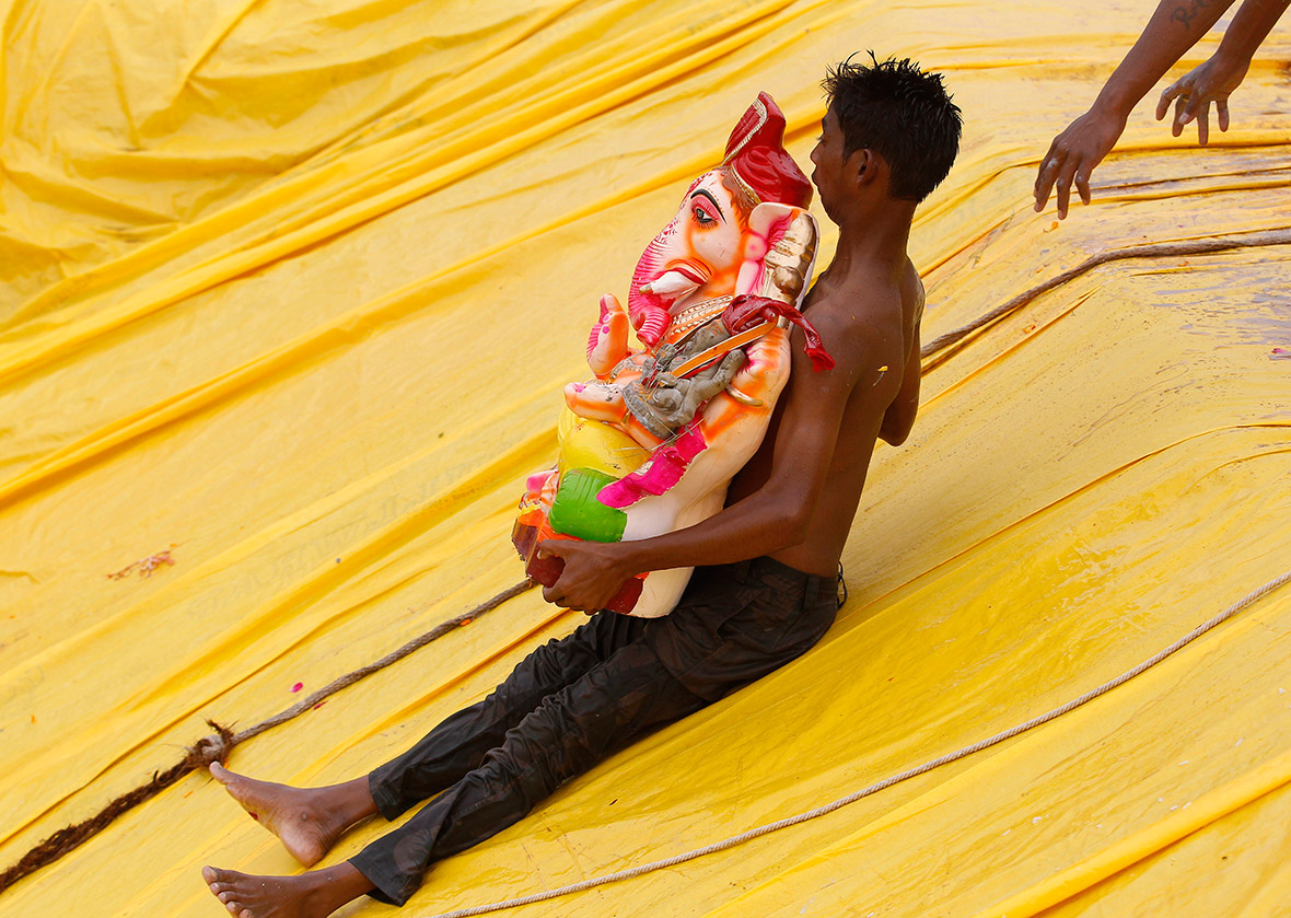 A young man carrying an idol of Ganesh slides down into a pond in the western Indian city of Ahmedabad