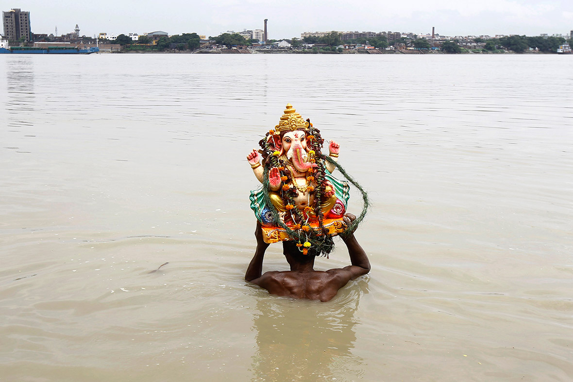 A devotee immerses an idol of the Hindu elephant god in the Ganges in Kolkata