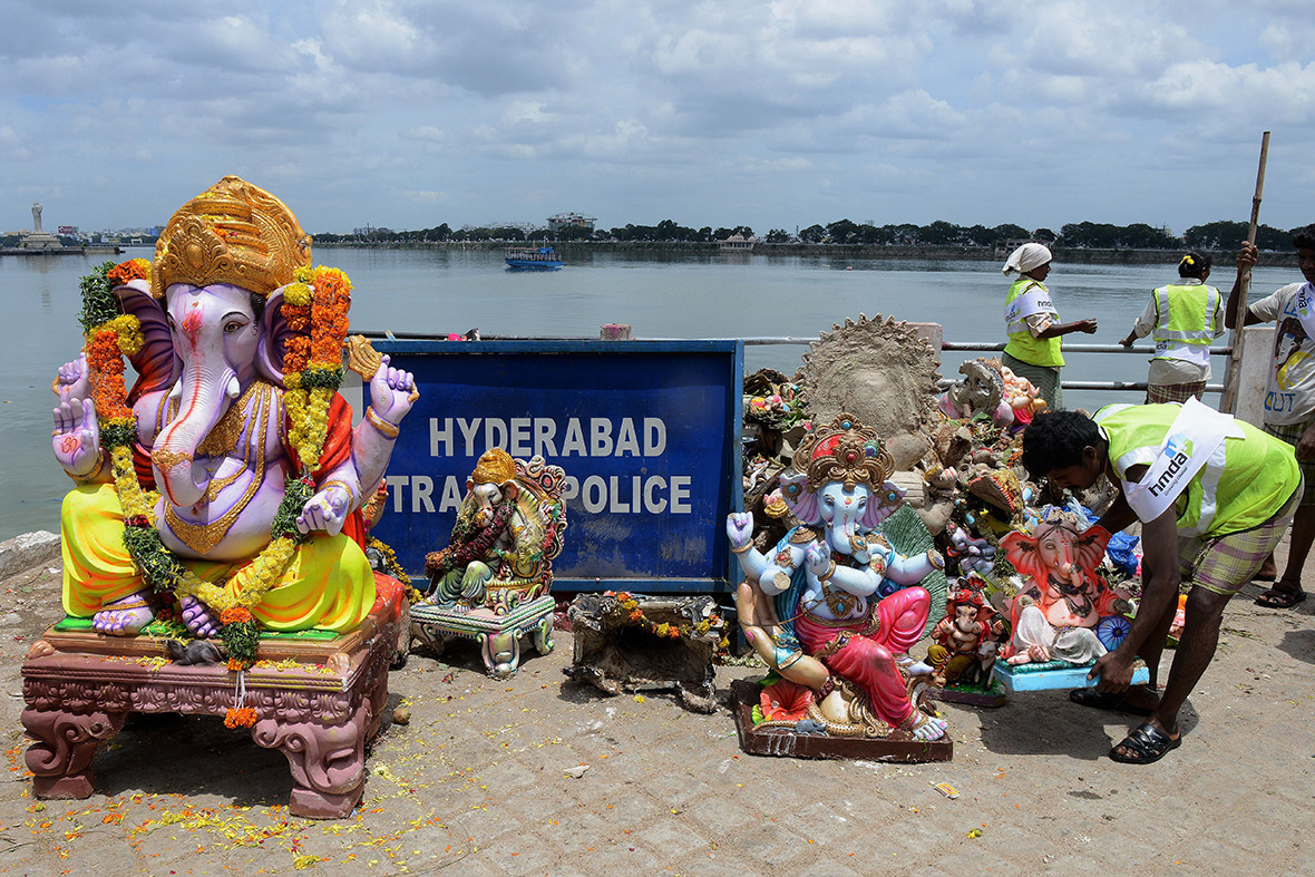 Indian Hyderabad Metropolitan Development Authority workers remove statues of Ganesh from the Hussain Sagar Lake after their immersion