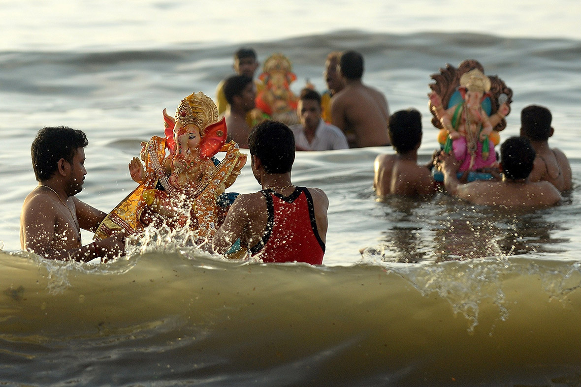 Hindu devotees carry idols of Ganesh into the Arabian Sea at Dadar Chowpatty beach in Mumbai