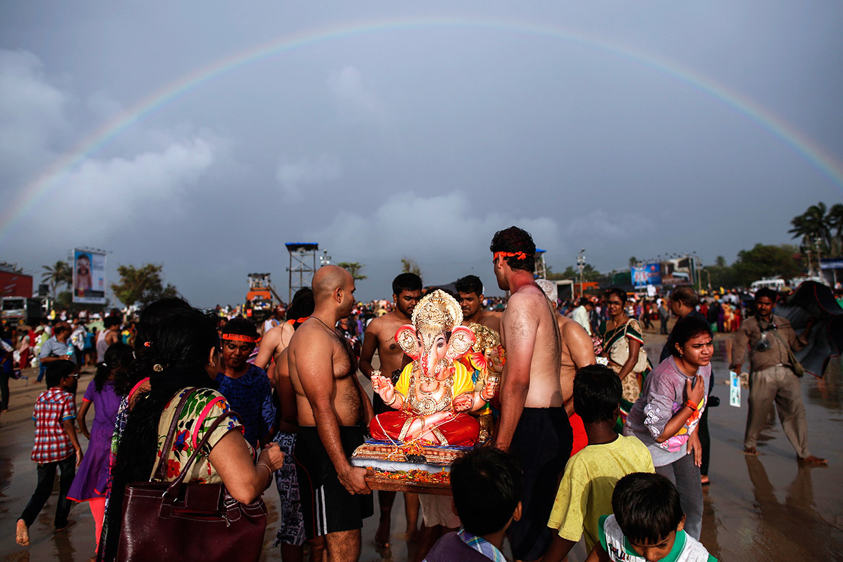A rainbow is seen as devotees carry a statue of Lord Ganesh, the deity of prosperity, into the Arabian Sea in Mumbai