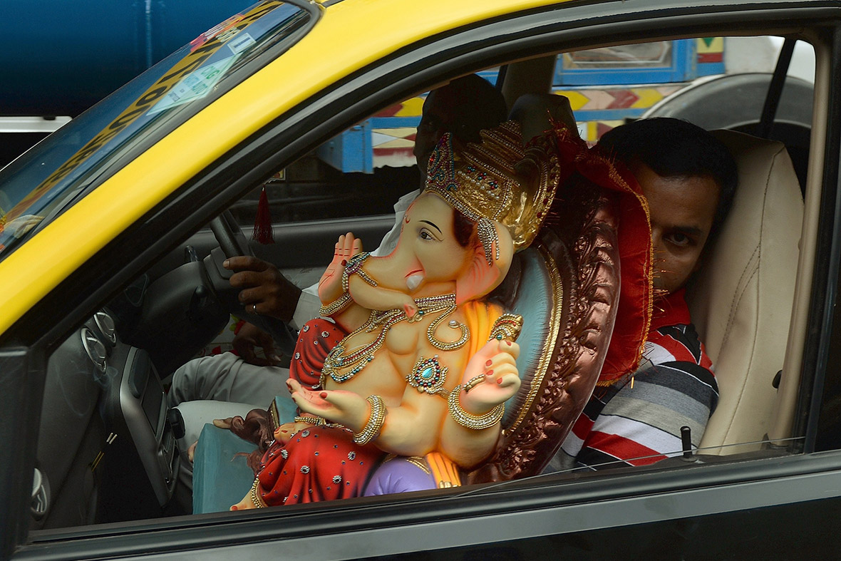 A man transports an idol of the elephant-headed Hindu god in a taxi cab in Mumbai
