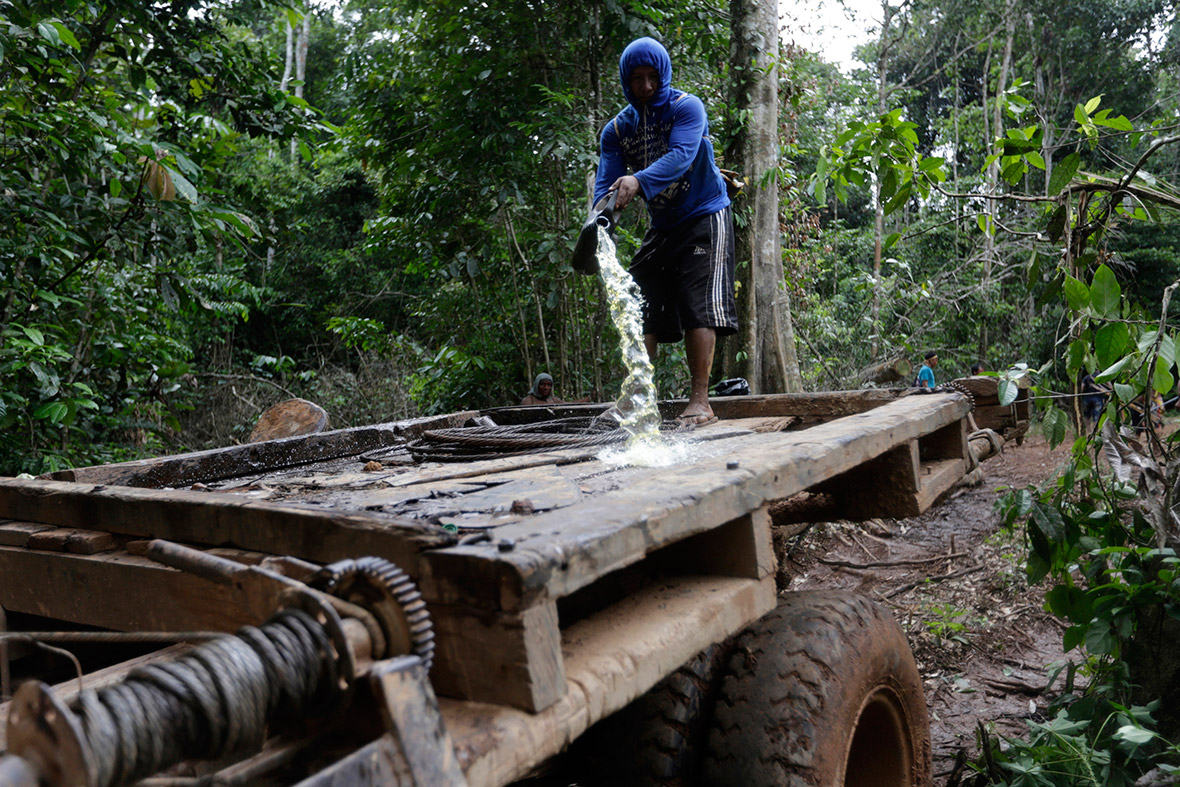 A Ka'apor man pours petrol on a logging truck in the Amazon