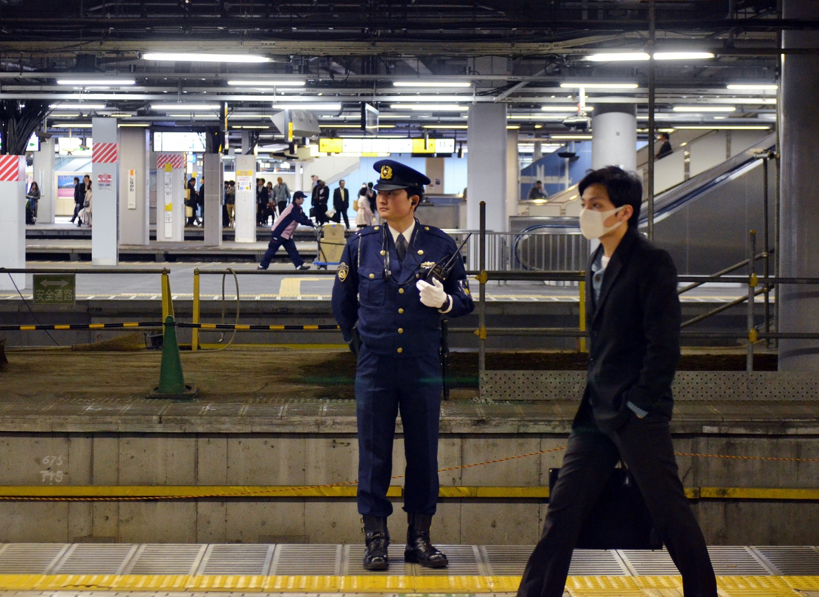 A police officer stands guard at a train station in Tokyo.