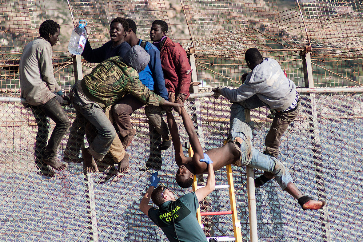 spain photo of golfers in melilla and african migrants clinging to border fence goes viral. Black Bedroom Furniture Sets. Home Design Ideas