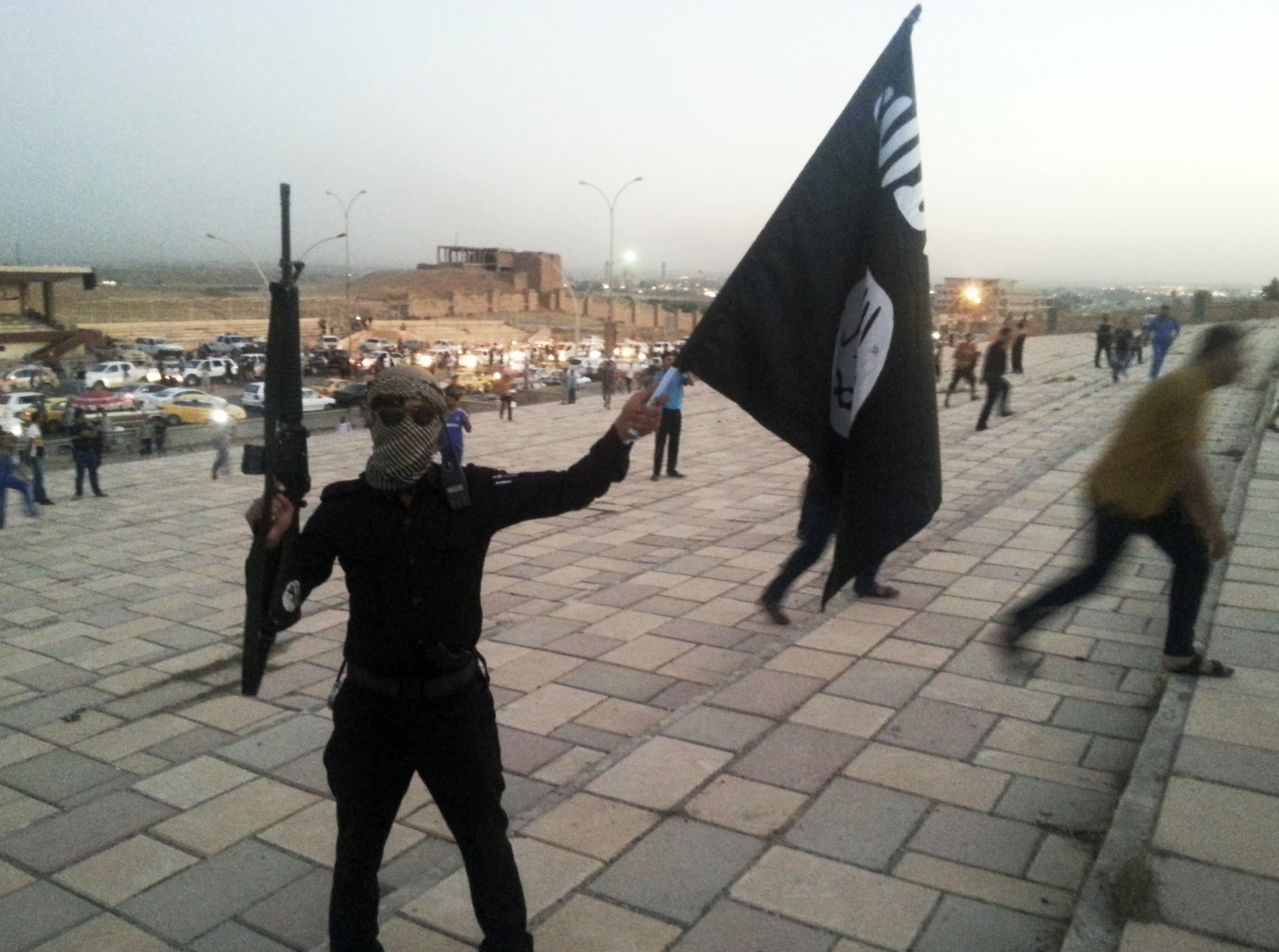 A fighter of the Islamic State holds an Isil flag and weapon.