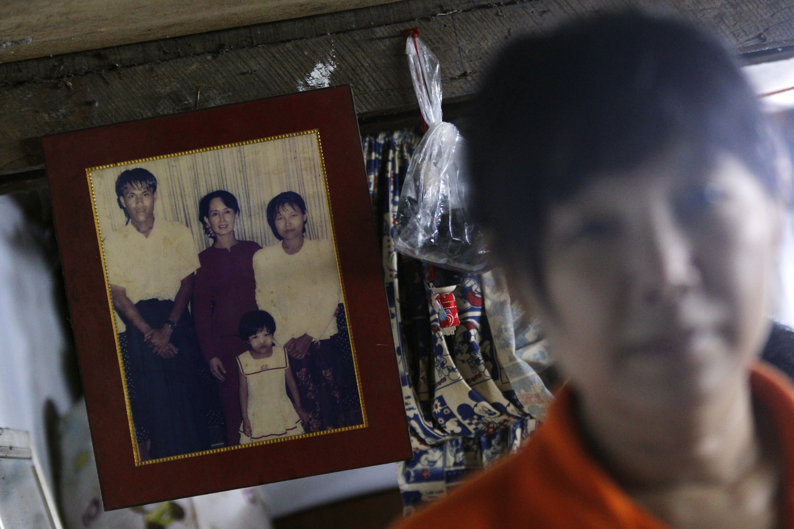 Than Dar, the wife of slain journalist Par Gyi, stands in front of a family photograph showing herself, her husband and daughter posing with Aung San Suu Kyi, during a Reuters interview at her home in Yangon