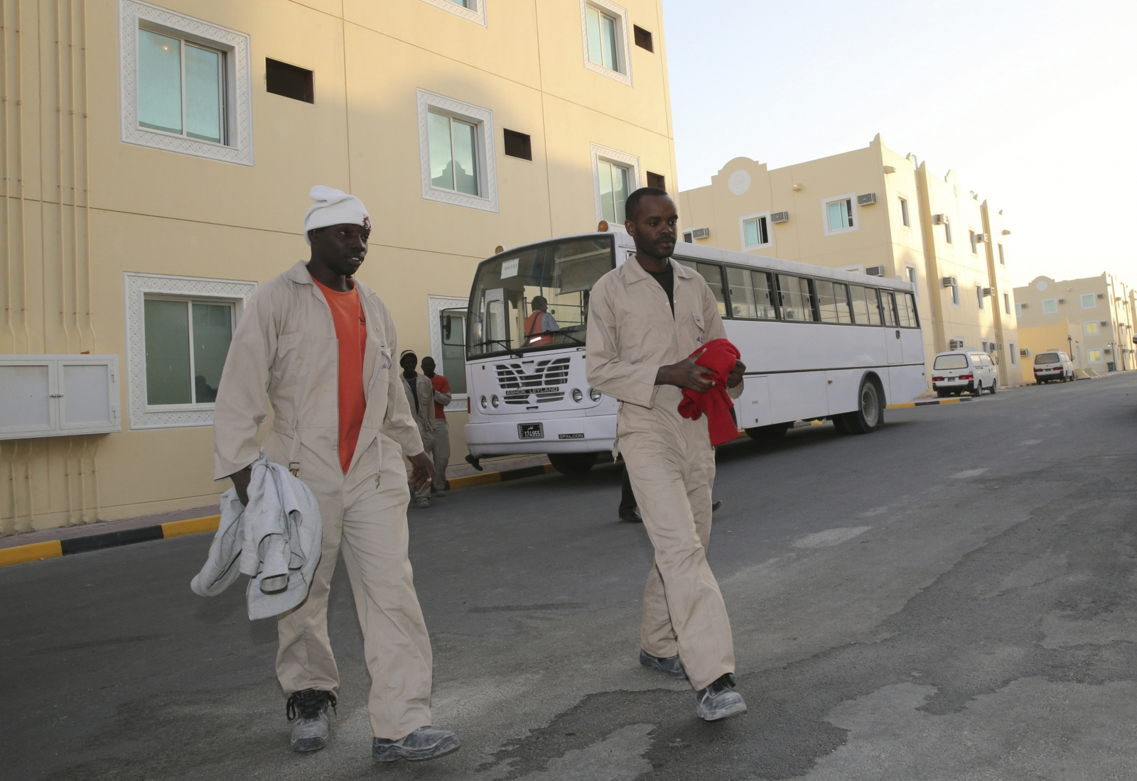 Labourers, who are working on the Qatar 2022 World Cup project, arrive at their accommodation in Doha