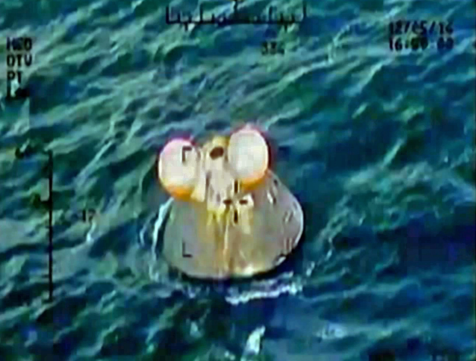 Footage from Nasa's Ikhana unmanned aerial vehicle, showing the Orion crew module safely landed in the water with two of its three main parachutes intact