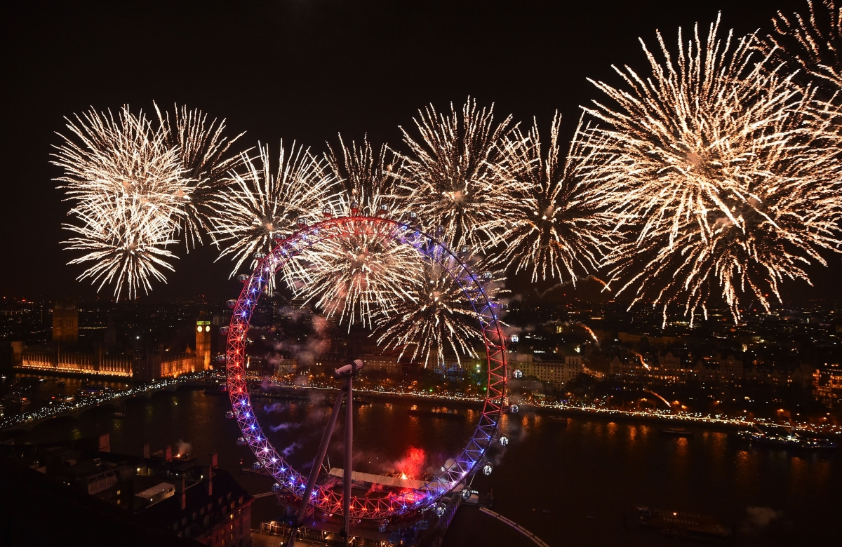 Fireworks explode above the Houses of Parliament and the London Eye on ...