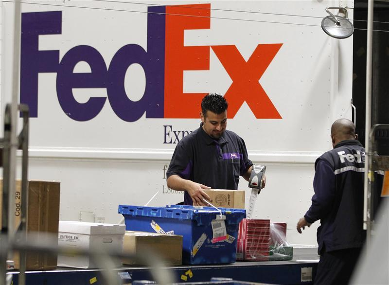 Handlers scan and affix a courier route label onto packages moving down the