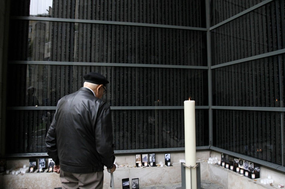 A man stands in front of a wall bearing the names of victims during the Holocaust memorial day