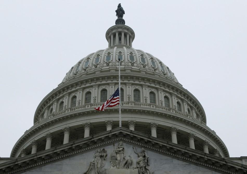 The United States flag flies at half staff in front of the U.S. Capitol dome in Washington