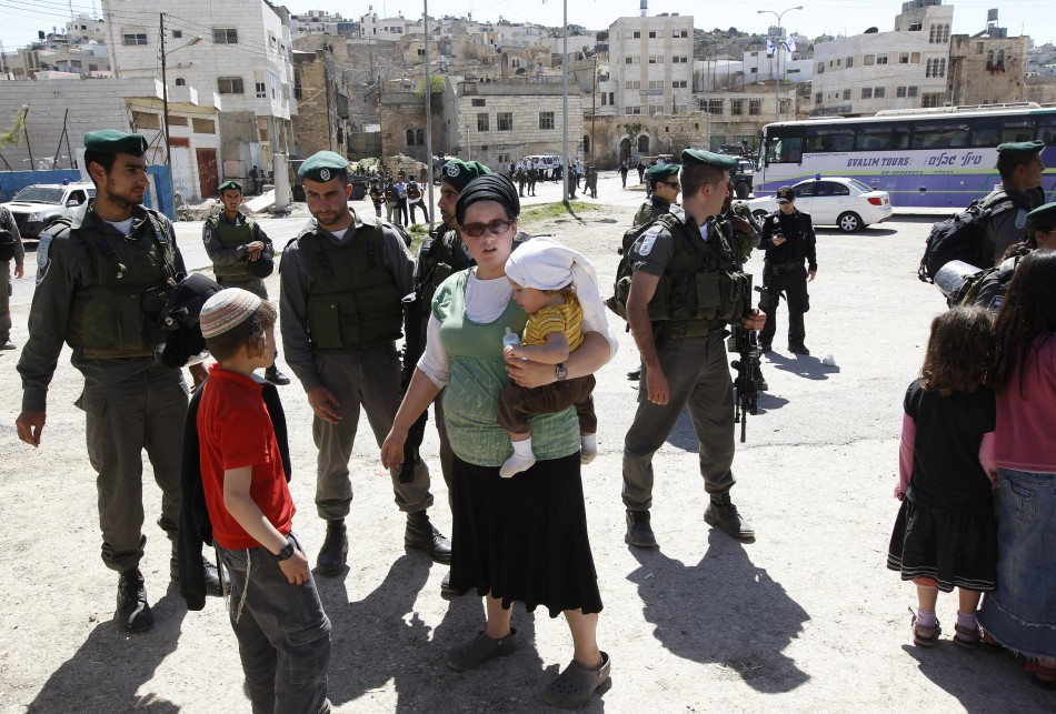 A Jewish settler stands near Israeli border policemen as they prevent her from reaching a building,